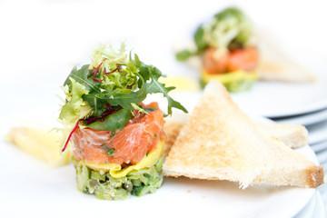 Salmon and avocado tartar with toast and lemon.