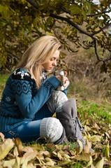 Девушка пьет из термоса чай