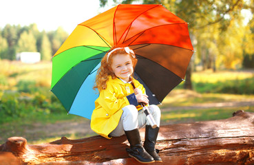 Autumn portrait little girl with colorful umbrella outdoors in p