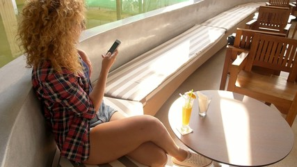 Attractive Woman in a Street Cafe Texting Message on Phone.