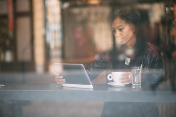 Young woman using tablet computer in coffee shop