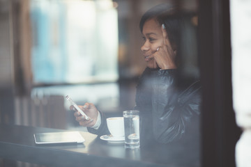 Young woman using phone in coffee shop