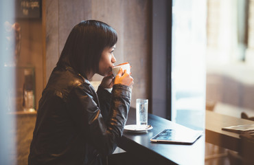 Young woman drinking coffee in modern cafe