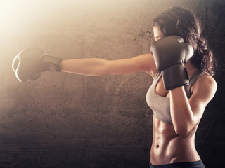 Fitness woman punching with boxing gloves