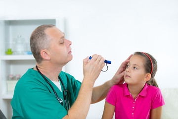 Eye doctor examining young girl patient - Ophthalmology