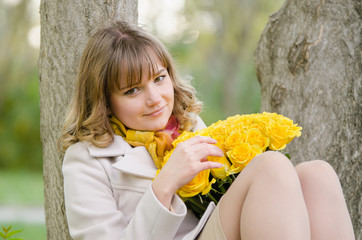 Sad girl with yellow roses, sitting in a tree