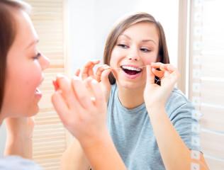 Beauty teenage girl flossing her teeth at home. Dental hygiene