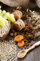 oatmeal in a clay bowl, stalks of oats, dried apricots, raisins,
