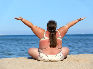 overweight woman on beach with hands up