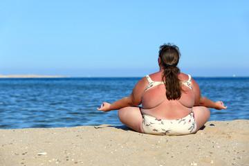 overweightl woman meditation on beach