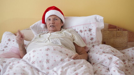 Happy senior woman in Christmas hat singing in the bed at home.
