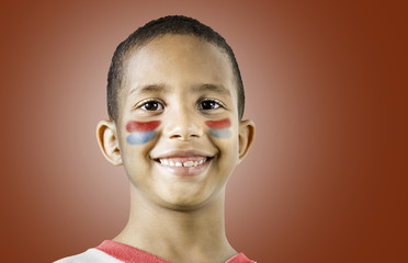 American little boy with his face painted with blue and red