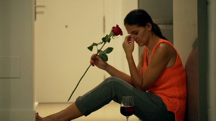 Heartbroken woman sitting on the floor with red rose and wine