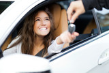 Woman receiving keys of her new car from dealer poster