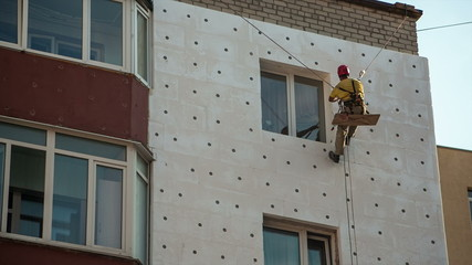 Industrial climber workers insulate the walls with Styrofoam
