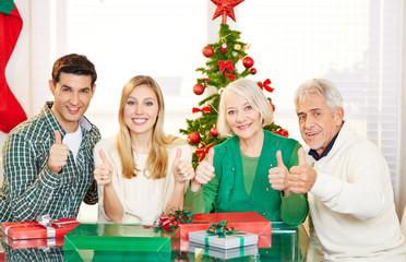 Paar und Senioren halten Daumen hoch an Weihnachten