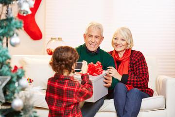 Enkel fotografiert Großeltern mit Smartphone