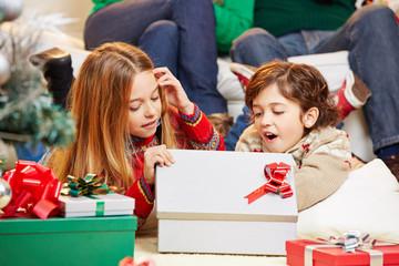 Glückliche Kinder öffnen Geschenke zu Weihnachten
