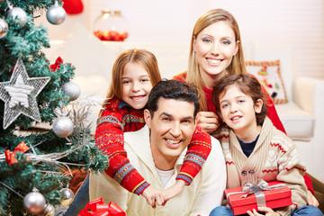 Glückliche Familie mit zwei Kindern an Weihnachten