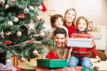 Familie zu Weihnachten mit Baum und Geschenken