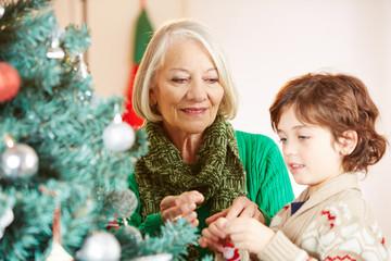 Enkel schmückt Weihnachtsbaum mit Großmutter zu Weihnachten