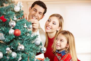 Familie schmückt Weihnachtsbaum zu Weihnachten