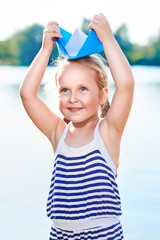 Cute little girl holding origami boat outdoors
