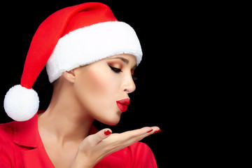 Happy Christmas Girl in Santa Hat Sending a Kiss