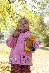 Little girl with basket and leaves in autumn park