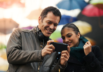 Cheerful man and woman friends looking at mobile smart phone
