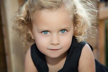 kleines blondes Mädchen blickt direkt in die Kamera