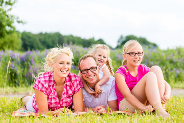 Family sitting on grass in lawn or field
