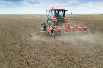 Farmer sowing crops with pneumatic seeding machine