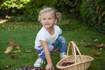 Mädchen sammelt Kastanien in einem Korb und freut sich