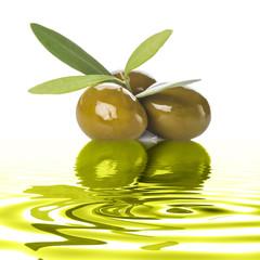 Aceitunas verdes con hojas reflejadas en aceite de oliva