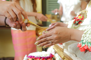 Hands pouring blessing water into bride's hands of Thai wedding.