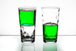 Two glasses, both half-full of green liquid. - 72523139