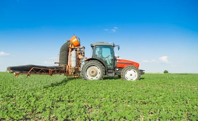 Farmer in tractor spraying soybeans