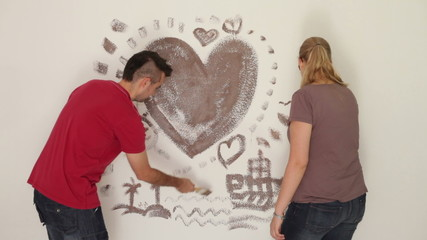 Happy couple in love painting pictures on the wall.