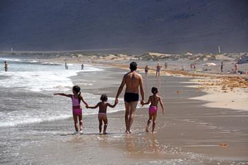 familia caminando por la playa de famara en lazarote
