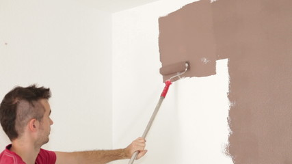 Man with paint roller painting wall