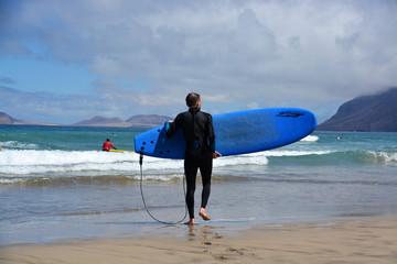 surfistas en playa de famara