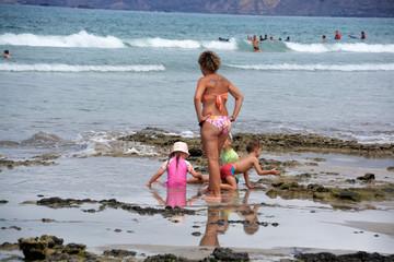 madre e hijos disfrutando un dia de playa