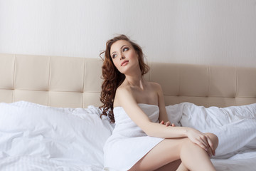 Dreamy woman posing in hotel bedroom