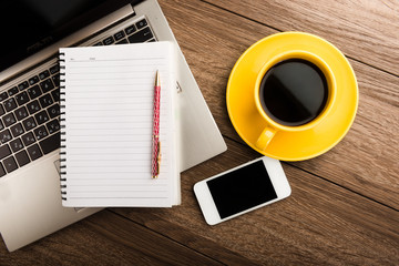 Office desk with devices?  notebook and coffee cup.