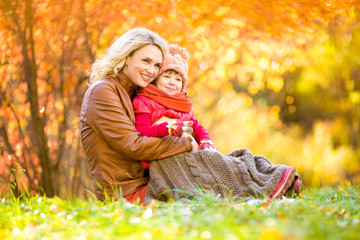 Happy mother and child outdoor in autumn park