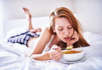 recovering woman in bed eating chicken soup while sick