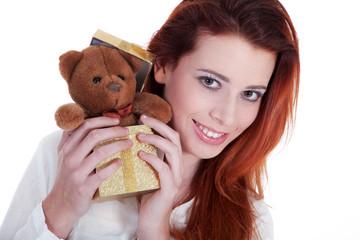 Junge rothaarige Frau überreicht goldene Geschenk Box mit Bär