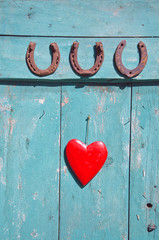 three  rusty horseshoe luck symbol and red heart on door