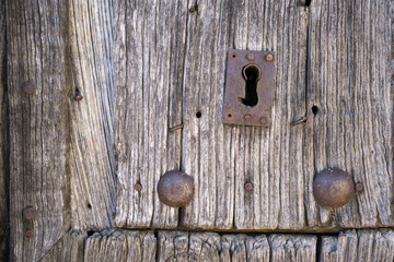 Front view of old lock and wooden door with iron nails